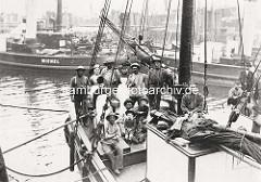 Historisches Bild einer Schifferfamilie und Mannschaft eines Frachtseglers im Hamburger Hafen.