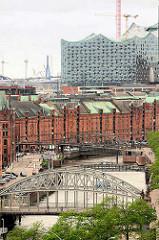 Blick zum Zollkanal und Speichergebäuden der Speicherstadt - im Vordergrund die Brooksbrücke, dahinter die Kibbelstegbrücke - alles wird überragt von der entstehenden Elbphilharmonie.
