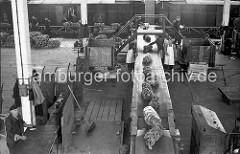 Die Bananenstauden werden von ihrem Lagerplatz im Kaischuppen auf einem Förderband zur Laderampe transportiert, wo die Südfrüchte in einen bereit stehenden Güterzug verladen werden. Vor der Verladung wird die Qualität der Ware geprüft.