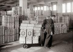 Zwei Lagerarbeiter transportieren Apfelsinenkisten mit einer Karre im Lager des Fruchtschuppens im Hamburger Hafen. Im Hintergrund sind die Kisten mit den Südfrüchten gestapelt; ca. 1930.