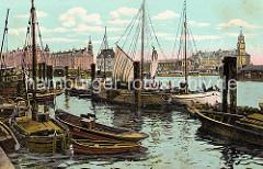Mehrere Ewer liegen am Baumwall - einige der flachbodigen Schiffe sind mit Seitenschwertern versehen, die die Abdrift verringern. Durch den geringen Tiefgang der Frachtsegler können die Schiffe hervorragend auf den tideabhängigen Gewässern der