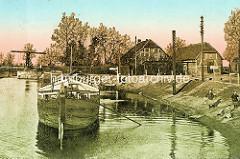 Alte Ansicht an der Elde Schleuse in Dömitz - ein Frachtschiff liegt am Ufer - Kinder spielen an Land; im Hintergrund die Klappbrücke.