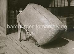 Ein großer Ballen wird von einem Hafenarbeiter von Hand mit Hilfe einer Sackkarre in den Kaischuppen transportiert; ca. 1934.