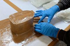 Mit Epoxidharz versehene Glasfaserstreifen werden für die Anfertigung des Masthalters um eine Form gedrückt.