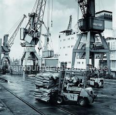 Der Gabelstaplerfahrer hat zwei Paletten mit Säcken auf seinen Gabelträger aufgenommen und fährt seine Last über die Kaianlage im Hamburger Hafen - im Hintergrund werden Container mit einen Kran auf das am Kai liegende Frachtschiff verladen.