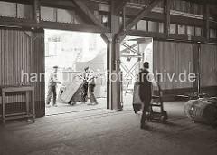 Hafenarbeiter transportieren Kisten mit der Sackkarre auf der Laderampe und im Lagerschuppen. Im Hintergrund liegt ein Frachtschiff am Kai; ca. 1932.