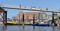 Blick vom Zollkanal zum Hamburger Binnenhafen - Barkassen liegen im Wasser; Touristen auf der Fussgängerbrücke / Kehrwiedersteg.