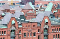Erneuerte Kupferdächer der Backsteinarchitektur in der Speicherstadt im Hamburger Stadtteil Hafencity - das Kupfer ist noch nicht oxidiert, während die hinteren Dächer und Windendächer an den Giebeln mit einer grünen Oxidationsschicht überzogen sind.