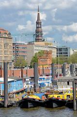 Barkassen und Arbeitsboote im Hamburger Binnenhafen - im Hintergrund die Hohe Brücke und der Kirchturm der St. Katharinenkirche.