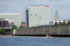 Bürogebäude an der Ericusspitze in der Hamburger Hafencity - Spiegelverlagshaus; daneben der Kupferturm vom Hamburger Rathaus; hohe Kaimauer - Sportboot in Fahrt auf dem Oberhafenkanal.