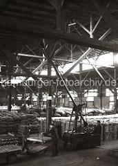 Mit einem Elektrolaufkran laden Arbeiter eine Partie Kupfer- barren auf den Anhänger eines Elektroschleppers. Das Hafenlager ist mit gestapelten Säcke und Baumwollballen gefüllt; ca. 1932.