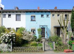 Einstöckige Reihenhäuser mit unterschiedlich farblich abgesetzer Fassade / Gartenzaun; Imbekstieg in Hamburg Stellingen.