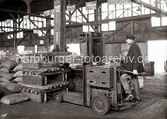 Mit einer Hubkarre stapelt der Fahrer Kupferbarren im Lager des Hamburger Hafens; auf der Gabel des Hubwagens der Marke YALE liegen mehrer Barren, die auf dicken Bohlen abgelegt werden.