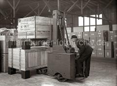 Ein Fahrer des Elektrohubwagens der Herstellerfirma Amme Luther stapelt zwei Holzkisten übereinander. Die Kisten stehen auf Blöcken als Abstandshalter, damit die Gabel und Vorderräder des Transportwagens Platz haben; ca. 1934.