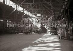 Mit mehreren elektrischen Transportkarren wird das Lagergut vom Kai heran gebracht; selbstfahrende Lagerkrane nehmen die Säcke auf und heben sie zu den Arbeitern auf den hohen Stapel. Dort wird die Lagerware von Hand verteilt; ca. 1934.