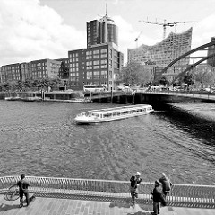 Blick über den Binnenhafen in die Hafencity Hamburgs - ein Ausflugsboot mit Hamburg Touristen passiert gerade die Niederbaumbrücke.