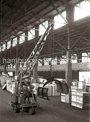 Arbeitserleichterung durch den Einsatz von Maschinen im Hafen Hamburgs: in einem Lagerschuppen fährt der Fahrer einen Papierballengreifer durch den Gang zu seinem Arbeitseinsatz; ca. 1932.