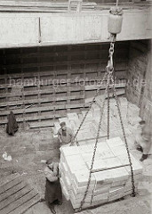 Die Ladung Rosinenkisten ist von den Stauern auf dem Ladegeschirr des Krans verstaut und wird aus dem Laderaum des Frachters gehievt; ca. 1932.