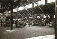 Unentwegt bringen die beladenen Elektrotransportkarren die angelandeten Säcke in die Lagerhalle des Hamburger Hafen. Auf dem schon gestapelten Sackgut nehmen die Arbeiter das Lagergut entgegen und verstauen die Ware auf dem hohen Stapel.