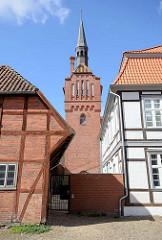 Kirchturm der Dömitzer Johanneskirche zwischen Fachwerkhäusern.