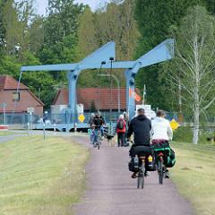 Fahrradfahrer und Spaziergänger auf dem Deich am Dömitzer Hafen - im Hintergrund die Klappbrücke über den Müritz Elde Kanal.