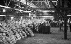 Die Bananen werden im Lagerschuppen von hölzernen Transportkisten geladen und in mehreren Schichten in dem riesigen Hafenschuppen gelagert. Der Fußboden des Gebäudes ist mit Steinen gemauert - eine massive Holzkonstruktion.