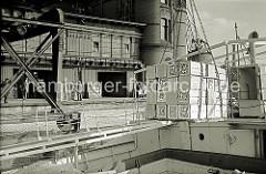 Eine Hieve Apfelsinenkisten hängt am Ladegeschirr über dem Laderaum des Schiffs - auf dem Kai das Laufrad und die Schiene des fahrbaren Halbportalkrans vor dem Fruchtschuppen.
