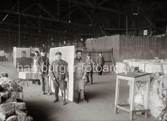 Mit Handhaken haben die Arbeiter die schwere Marmorplatte aufgenommen und tragen diese an ihren Bestimmungsort; im Hintergrund hat ein sind Kisten auf eine Sackkarre gestapelt; ca. 1932.