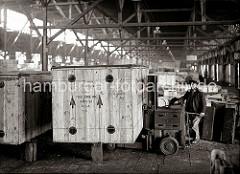 Eine grosse Holzkiste mit der Aufschrift Made in USA wird von einem Lagerarbeiter mit einem Hubwagen der Herstellerfirma YALE an ihrem Platz im Lagerschuppen abgestellt; ca. 1934.