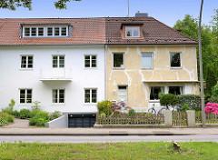 Alt + Neu - restaurierte, frisch gestrichene Hausfassade - Renovierung in Vorbereitung, Risse sind verspachtelt - einstöckiger Wohnblock in Hamburg Eissendorf.