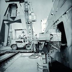 Der Fahrer eines Gabelstaplers fährt auf die Laderampe auf dem Kai und schiebt eine Palette mit Kisten durch eine Luke in der Seitenwand des Frachters; ca. 1972.