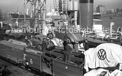 Die Arbeiter stehen auf der oberen Plattform des Güterwaggons und überwachen die Verladung eines Volkswagens - der fabrikneue Käfer schwebt im Ladegeschirr über der Kaianlage am Oderhafen und wird gleich in den Laderaum des Frachter gehoben.