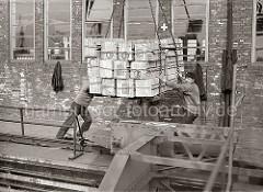 Ein Kranführer setzt die Hieve Apfelsinenkisten auf der Galerie des Fruchtschuppens ab - Lagerarbeiter dirigieren die Ladung an ihren Platz; im Vordergrund das Schienensystem mit Führung des Halbportalkrans; ca. 1930.
