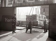 Ein Kran setzt seine Last Apfelsinenkisten auf der Galerie eines Fruchtschuppens ab - Lagerarbeiter dirigieren die Hieve an ihren Platz; der Lagermeister beobachtet die Arbeiter.