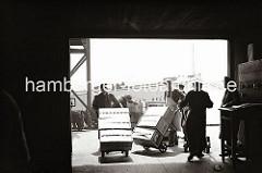 Transportarbeiter bringen die vom Frachter angelandeten Fruchtkisten mit Sackkarren in den Lagerraum des Fruchtschuppens A am Versmannkai des Baakenhafens. Jeweils drei der Holzkisten werden mit einer Fuhre transportiert. Im Hintergrund die K