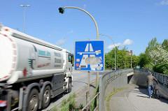 Autobahnauffahrt in Hamburg Stellingen - ein Tanklastzug fährt Richtung Autobahn A7 - ein Mann schiebt sein Fahrrad zur Fussgänger Unterführung unter der Autobahn / Strasse.