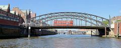 Zollkanal an der Hamburger Speicherstadt - lks. Kupferdächer der Speichergebäude - ein roter Dppeldeckerbus der Stadtrundfahrt auf der Brooksbrücke - im Hintergrund der Binnenhafen.