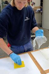 Glasfasergewebe wird mit Epoxidharz eingestrichen.
