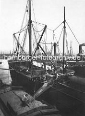 Hansahafen - Dampfer beim Kornlöschen im Hamburger Hafen; ein Arbeiter verteilt das Korn mit der Schaufel auf der Schute.