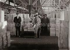 Die Lagerarbeiter nehmen die Kisten mit den Rosinen von dem Transportkarren auf und bringen sie auf der Schulter zur dem Lagerplatz. Die Kisten gefüllt mit getrockneten Weinbeeren sind in dem Fruchtschuppen mannshoch aufgestapelt; ca. 1932.