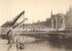 """Blick zur Brooksbrücke, die über den Zollkanal zum Hamburger Freihafengelände und der Speicherstadt führt. An den Kaimauern des Kanals an der Strasse """"Bei dem Neuen Krahn"""" stehen zwei Kräne die die Ladung von den Schiffen an Land hieven."""
