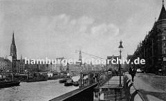 Fassade der Speicherstadt am Kehrwieder - der Zollkanal bildet die Freihafengrenze. Im Binnenhafen liegen Schuten beladen mit Kohle; ein Kahn wird mit einem Schlepper auf dem Kanal gezogen. Die Kirchtürme von der St. Nikolaikirche und der St. Kat