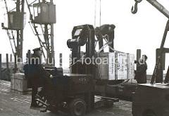"""Mit Hilfe eines Hubwagens wurde die große Holzkiste aus dem Lagerschuppen auf den Hafenkai gefahren. Dort bereiten zwei Hafenarbeiter die Kiste für die Verladung vor. Auf der Stirnseite der Kiste ist u.a. die Bezeichnung """"Made in Germany""""."""
