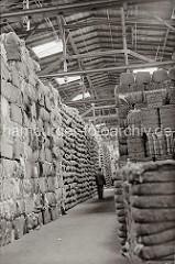In einem Speicher im Hamburger Hafen sind Wollballen und andere Güter in Säcken bis unter das Dach gestapelt. Ein Lagerarbeiter geht durch den Gang zwischen der Lagerware; ca. 1934.