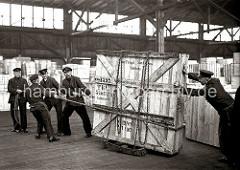 Fünf Mann arbeiten daran eine große Holzkiste mit Glasscheiben durch das Lager im Hamburger Hafen zu transportieren. Die Kiste steht auf Schwerlastrollen und ist mit einer Eisenkette an dem Gestell fixiert.