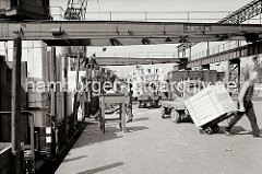 Ein Güterzug wird an der Laderampe entladen, er hat Stühle und Kisten geladen. Ein Arbeiter transportiert eine grosse Holzkiste mit einer Sackkarre, ein anderer Hafenarbeiter fährt gerade mit der Karre die Laderampe auf den Güterwaggon hoch.