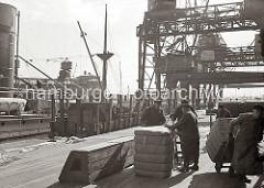 Große Ballen sind an Land gebracht worden - sie wurden mit dem Kran auf der Laderampe des Lagerschuppens abgesetzt. Dort heben zwei Kaiarbeiter die schwere Last an, damit ein weiterer Arbeiter mit seiner Sackkarre die Ladung aufnehmen kann.