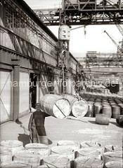Zwei Holzfässer hängen im Ladegeschirr am Haken des Halbportalkrans im Hamburger Hafen. Weitere Tonnen stehen auf der Laderampe - im Hintergrund Güterwaggons der Hafenbahn; ca. 1930.