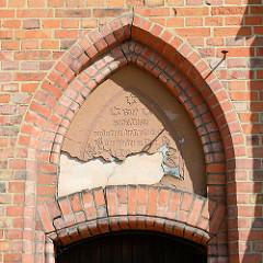Fassade Kirchturm der Johanneskirche Dömitz; neugotische Hallenkirche, erbaut 1872 - Architekt Oppermann. Inschrift Gott ist Liebe; und wer in der Liebe bleibt, der bleibt in Gott und Gott in ihm.
