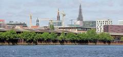 Blick über den Oberhafenkanal zur Hamburger Hafencity; Lagerschuppen hinter Sträuchern am Oberhafen - Baukräne; Kirchtürme der Hansestadt Hamburg.